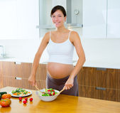 Beautiful pregnant woman at kitchen preparing salad — Stock Photo