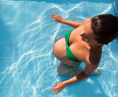 Beautiful pregnant woman sun tanning at blue pool — Stock Photo