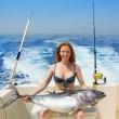 Bikini fisher woman holding bluefin tuna on boat — Stock Photo #13828338