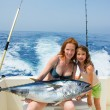 Bikini fisher woman and daughter with bluefin tuna — Stock Photo #13828364