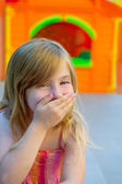 Blond kid girl funny gesture hand in mouth — Stock Photo
