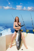 Bikini fisher woman holding bluefin tuna on boat — Stock Photo