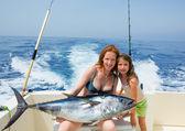 Bikini fisher woman and daughter with bluefin tuna — Stock Photo