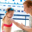 Children girl with mother applying sunscreen - Stock Photo