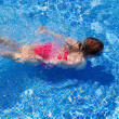 Bikini kid girl swimming on blue tiles pool - Foto Stock