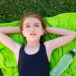 Children girl relaxed lying on towel over green grass — Stock Photo