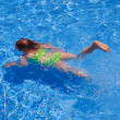 Stock Photo: Children gilr swimming underwater in blue pool