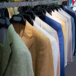 Colorful male suits in row in a hanger — Stock Photo