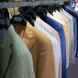 Colorful male suits in row in a hanger - Stock Photo