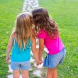 Friends sister girls whispering secret in ear in garden — Stock Photo