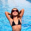 Royalty-Free Stock Photo: Bikini kid girl with sunglasses in blue pool