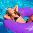 Children girl relaxed on purple inflatable pool ring — Stock Photo #13835493