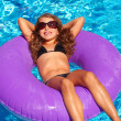 Children girl relaxed on purple inflatable pool ring — Stock Photo #13835534