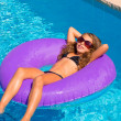 Children girl relaxed on purple inflatable pool ring — Stock Photo #13835678