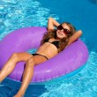 Children girl relaxed on purple inflatable pool ring — Stock Photo #13835727