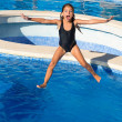Children girl jumping to the blue pool black swimsuit - Stock Photo