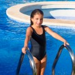 Children girl on the blue pool stairs black swimsuit — Stock Photo