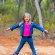 Royalty-Free Stock Photo: Kid girl climbing tree trunks with open arms