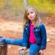 Children girl relaxed on a tree trunk in the forest — Stock Photo