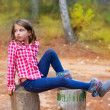 Children girl relaxed on a tree trunk in the forest — Stock Photo #13839863