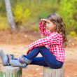 Kid girl sitting in forest trunk looking far away - Stock Photo