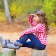 Kid girl sitting in forest trunk looking far away - Photo