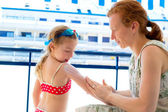 Children girl with mother applying sunscreen — Stock Photo