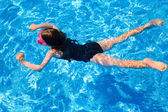 Bikini kid girl swimming on blue tiles pool in summer — Stock Photo