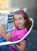Smiling girl sitting in outdoor aluminium chair — Stock Photo