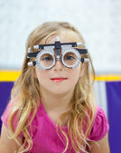 Blond children girl with optometrist diopter glasses — Stock Photo