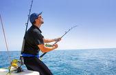 Barco de pesca costa afuera de mar azul con pescador — Foto de Stock