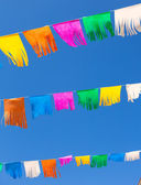 Colorful tissue Paper fringe garland under blue sky — Stock Photo