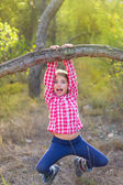 Children girl swinging in a trunk in pine forest — Stock Photo