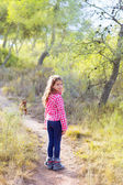 Children girl walking in the pine forest with dog — Stock Photo