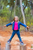 Kid girl climbing tree trunks with open arms — Stock Photo