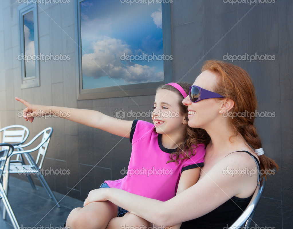Children girl daughter sitting on mother lap pointing finger away — Stock Photo #13832149