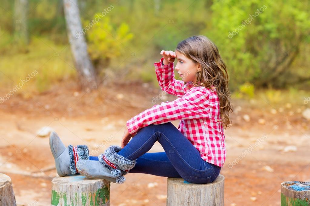 Kid girl sitting in forest trunk looking far away with hand in forehead — Stock Photo #13839887