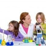 Children girlas and teacher woman at school laboratory — Stock Photo #16085439