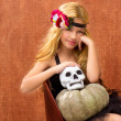 Halloween kid girl with pumpkin and skull smiling - Stock fotografie
