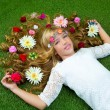 Blond spring girl with flowers on hair over grass — Stock Photo