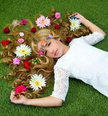 Blonďatá jarní dívka s květinami na vlasy trávě — Stock fotografie