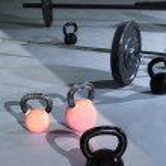 Kettlebells at crossfit gym with lifting bars — Stock Photo