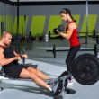 Gym couple with dumbbell weights and fitness rower — Stock Photo