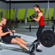 Gym couple with dumbbell weights and fitness rower - Stockfoto