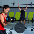 Girl dumbbell and man weight lifting bar workout — Stock Photo #18028059