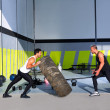 Crossfit flip tires men flipping each other - Stock Photo
