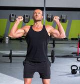 Uomo di palestra con manubri esercizio crossfit — Foto Stock