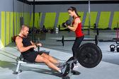 Gym paar met halter gewichten en fitness roeitoestel — Stockfoto