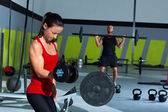 Girl dumbbell and man weight lifting bar workout — Stock Photo