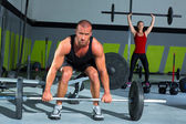 Gym with weight lifting bar workout man and woman — Zdjęcie stockowe